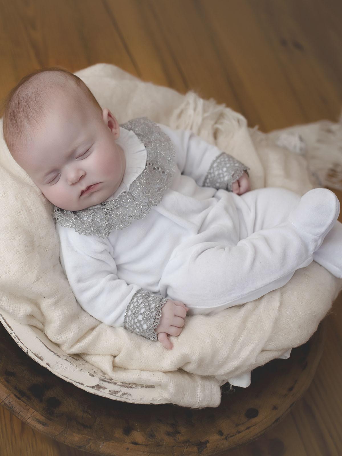 Babygrow em veludo branco para bebé. Gola e punhos com renda de cor prateado.